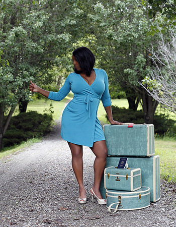 Ebony escort Andrea Davis with her luggage and wearing a short green dress, thumbing a ride on a gravel road