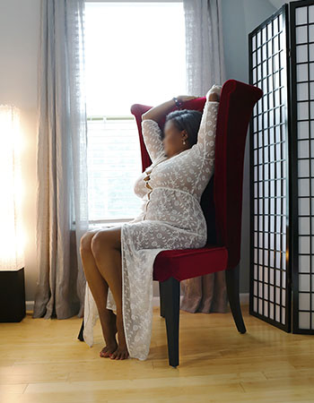Ebony escort Euphemia sitting in a red chair next to a window, wearing a sheer white dress
